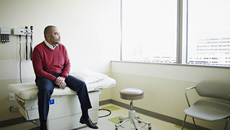 A man in a red shirt and blue pants waiting on a doctor's bed in a doctor's room. He's starting out the window.