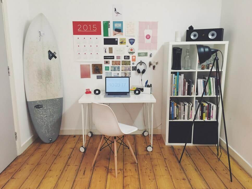 A room with a picture of a surfboard, a white table with a laptop on it, next to a lamp on a tripod and a bookshelf.
