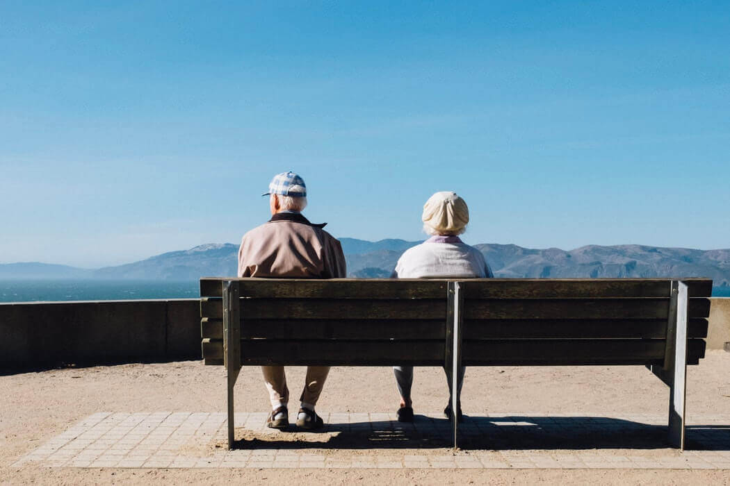 Two seniors sitting on a bench at a scenic overlook with mountains and blue skies