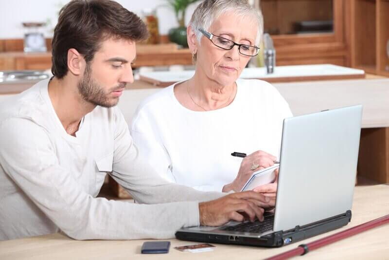 A young man helping a senior with her laptop. They are sitting next to each other while the silver laptop sits in front of them. Both are looking at the screen.