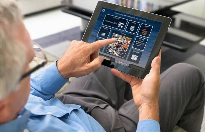 A man with a blue dress shirt and tan dress pants sitting down and using a tablet to control devices in his smart home