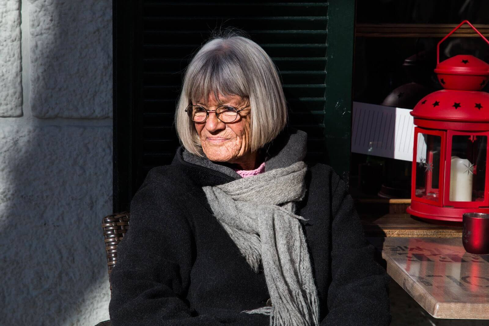 A lady with silver hair, a black jacket and a gray scarf, sitting at a table outside in the sunlight