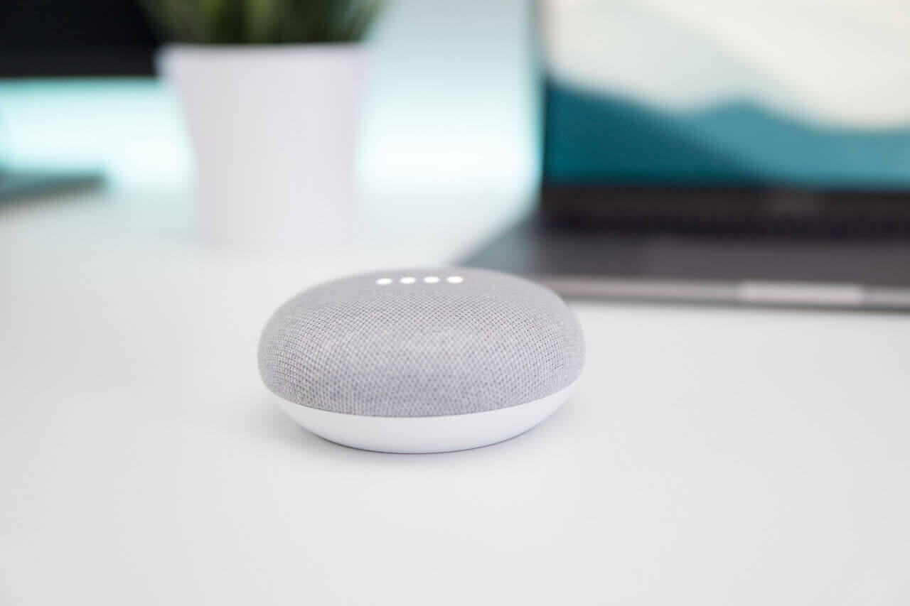 a white smart speaker sitting on the white desktop with a laptop blurred out in the background