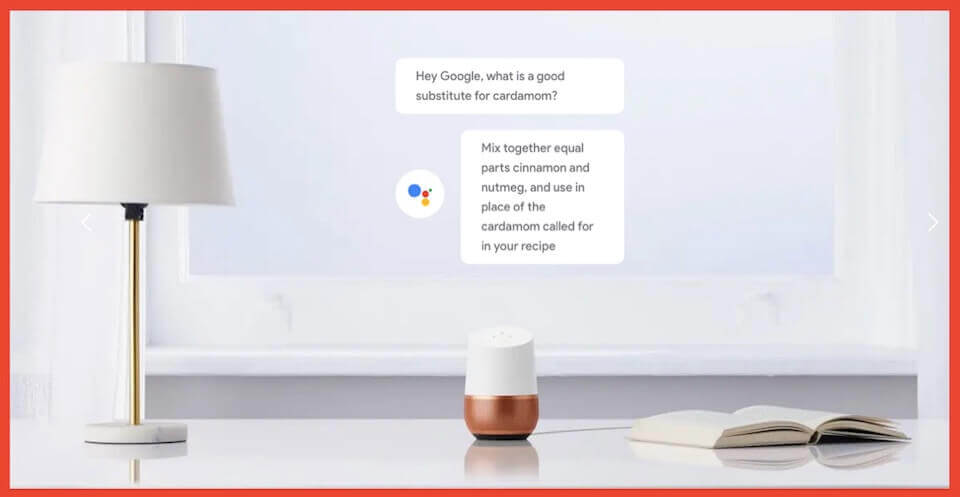 A Google Home sitting on a white desk next to an open book and lamo