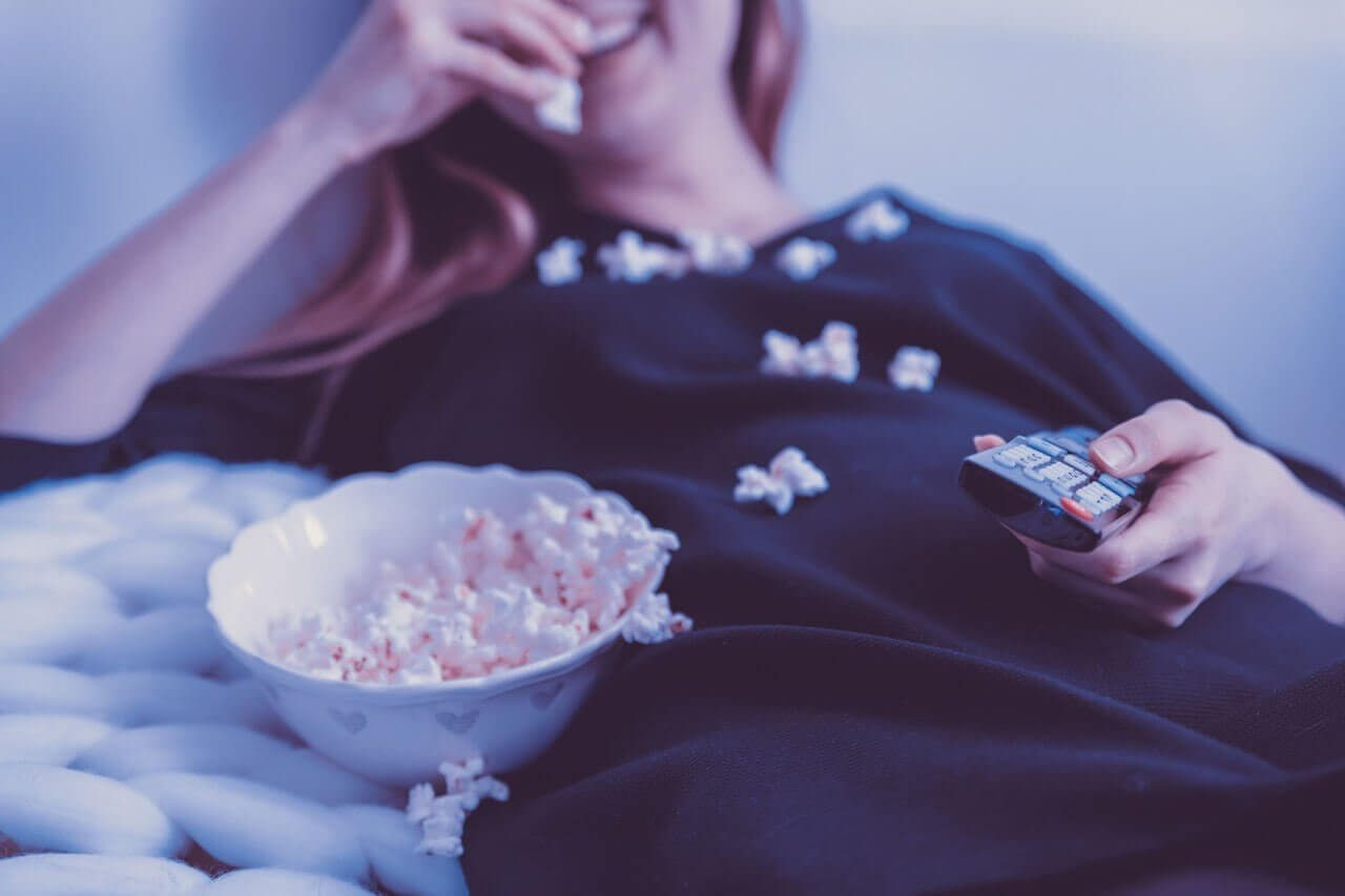 A woman sitting on a couch, smiling, and eating popcorn. She has popcorn all over herself.
