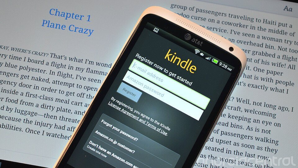 A phone with the Kindle app login page on its screen. In the background is are pages of an open book