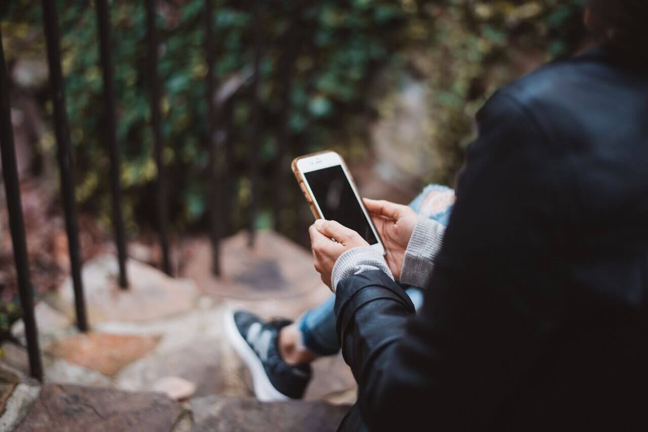 An individual sitting outside on steps and looking at their phone.