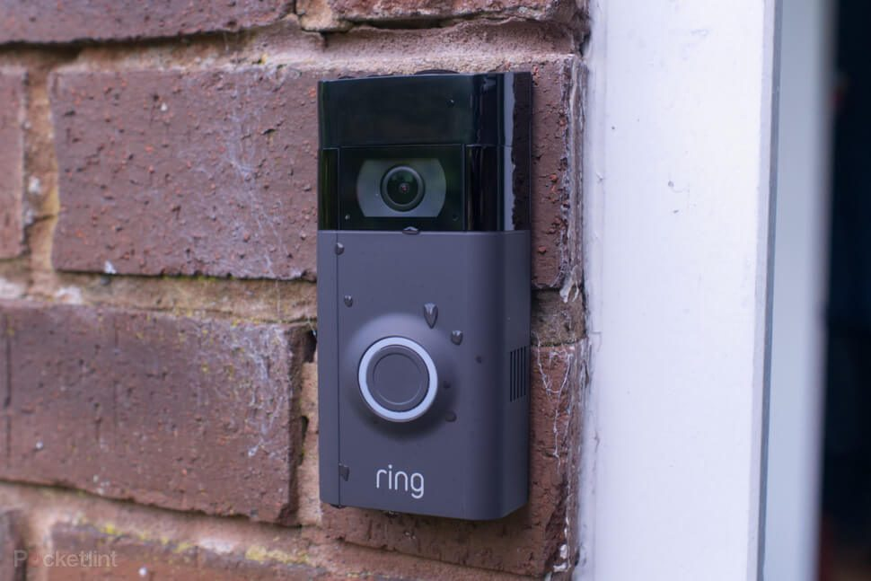 A Ring (name brand) doorbell installed on a brick wall outside