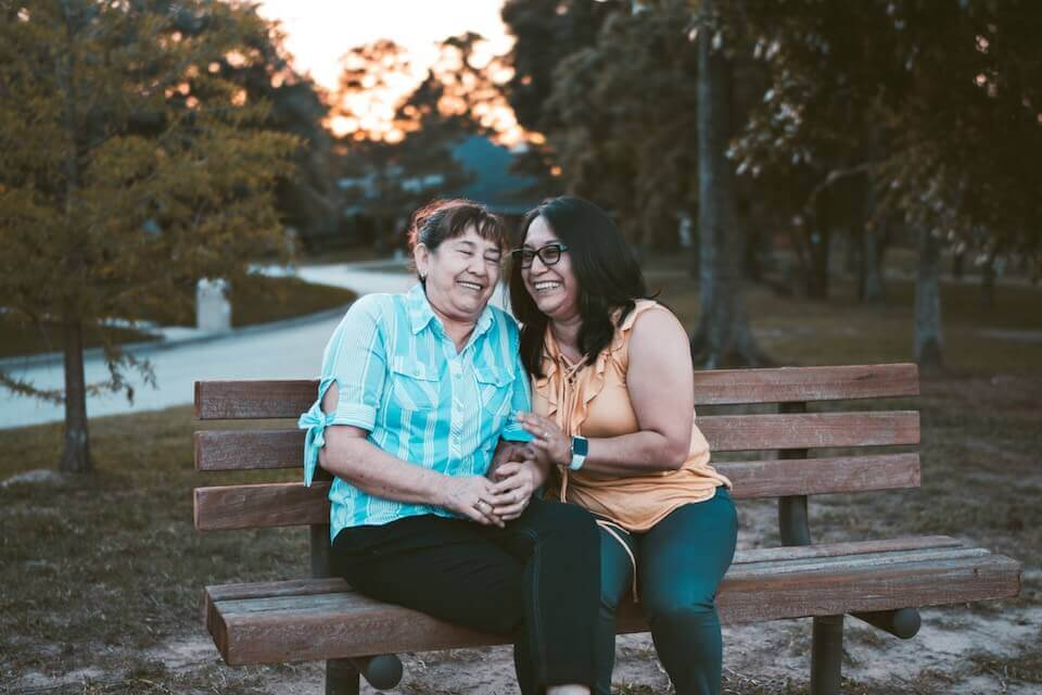 A mother and daughter sitting on a park bench holding each other and laughing together