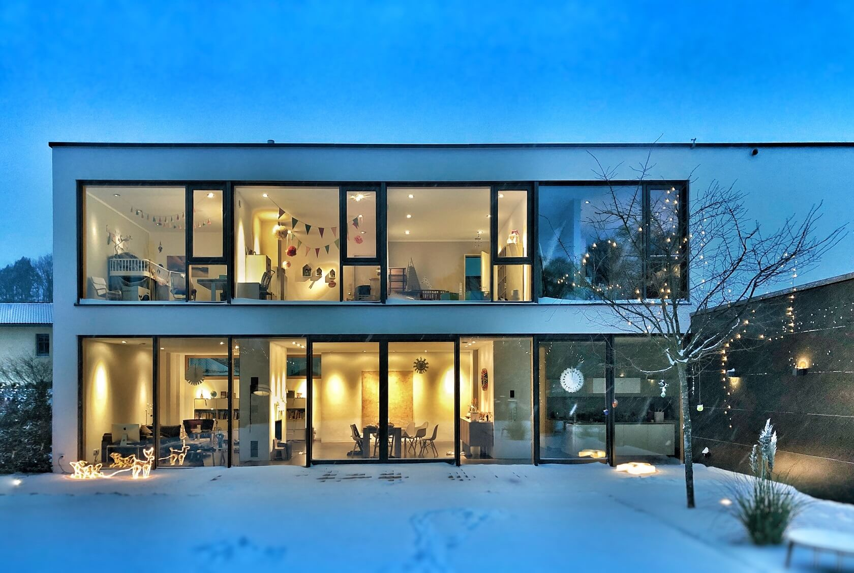 A house with many windows and glass at dusk with snow on the lawn