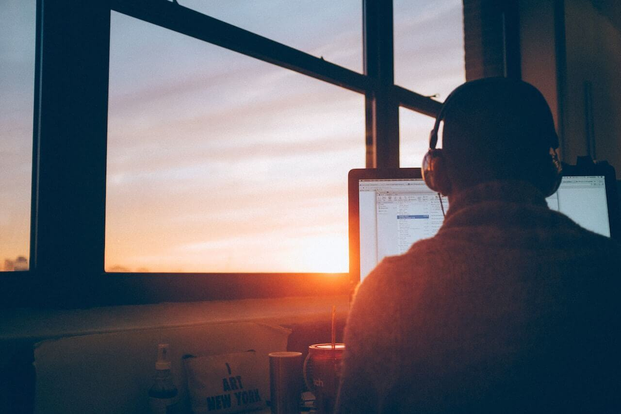 A man sitting at his computer with headphones on. In the background is an orange sunset.