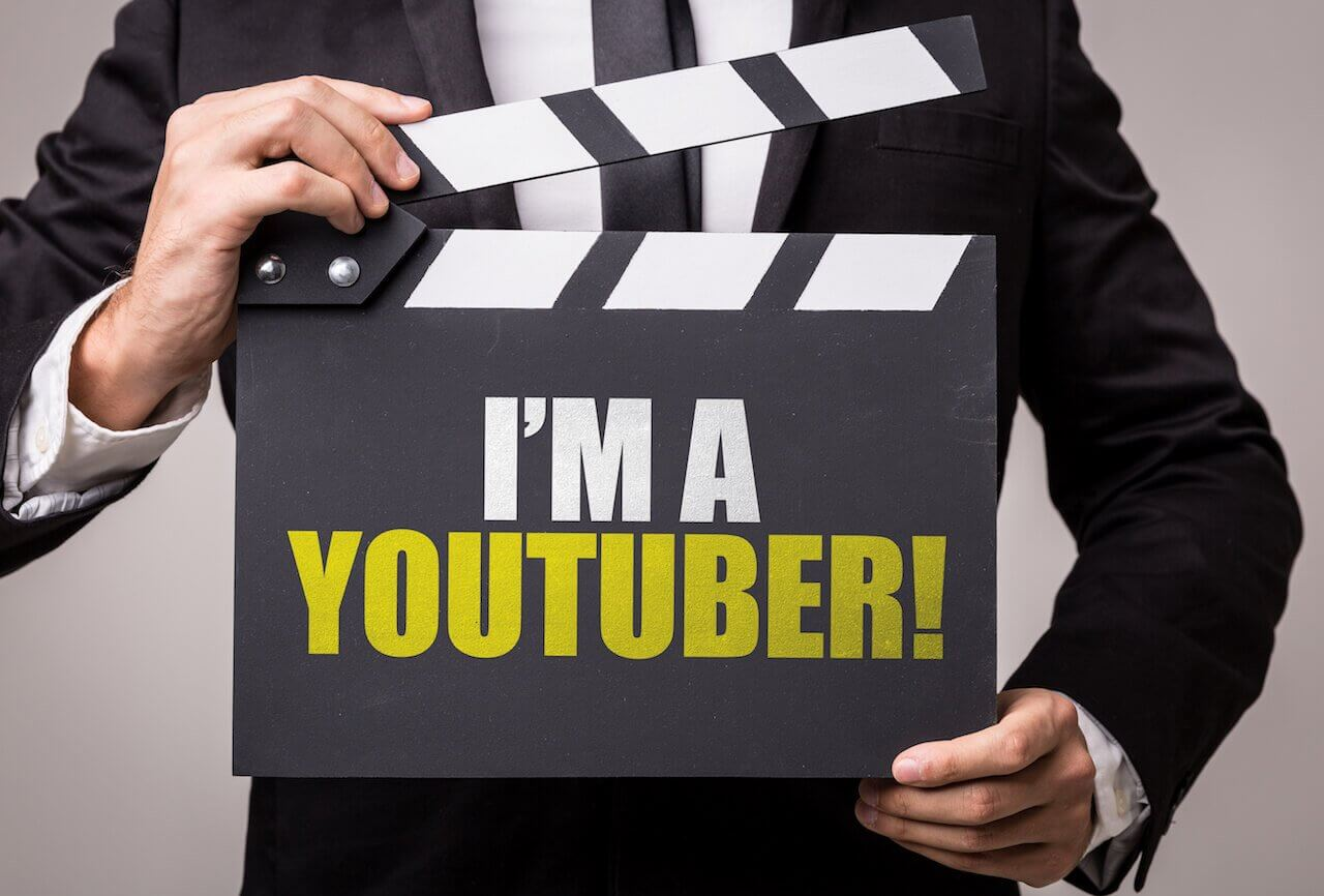 A person in a black suit and black tie holding a action/cut sign that says I'm a YouTuber!